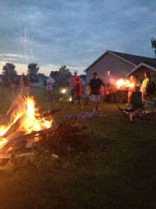Kids playing with sparklers and bonfire.